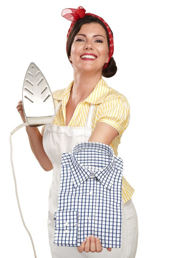 happy beautiful woman housewife ironing a shirt