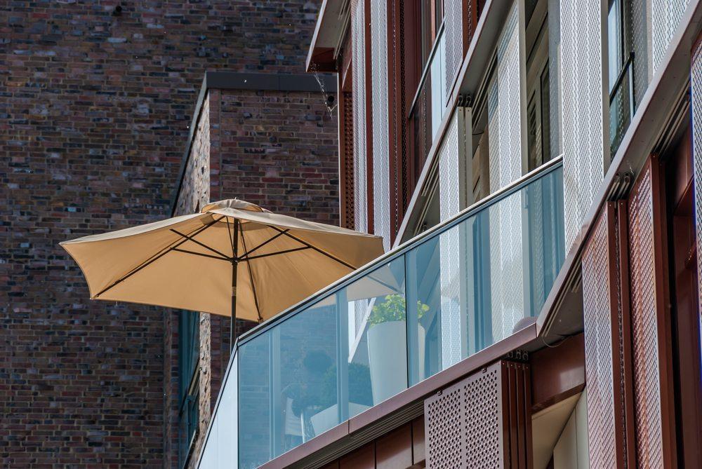 Wer einen Balkon bestücken will, hat oftmals wenig Platz, um einen klobigen Schirmständer unterzubringen. (Bild: HBpictures / Shutterstock.com)