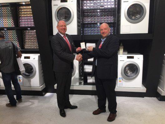 """Wolfgang Pauler (Testchef von CHIP, rechts im Bild) übergibt den Preis für den Hersteller des Jahres an Miele auf der IFA in der Kategorie """"Waschmaschinen"""". (Bild: © CHIP)"""