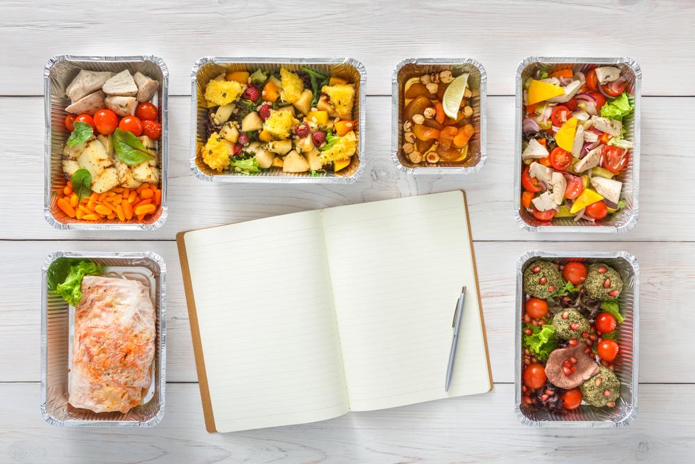 Ein Notizbuch ist umgeben von kleine Mahlzeiten