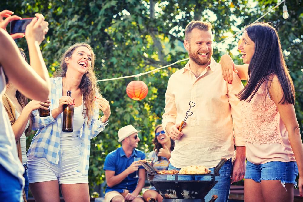 Gruppe von Freunden, die im Garten Grill machen. Konzept der guten und positiven Stimmung mit Freunden