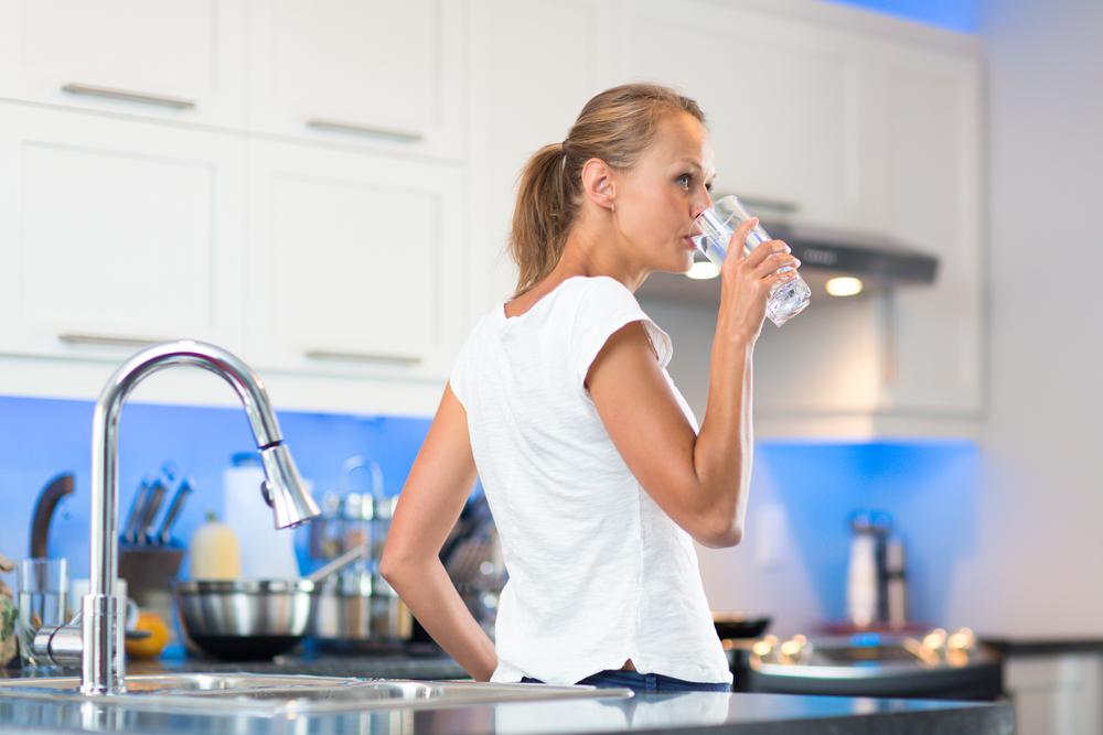 Hübsche, junge Frau in ihrer modernen, sauberen und hellen Küche, gießt sich ein und trinkt ein Glas kaltes Leitungswasser